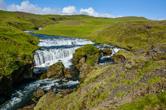 Countryside with trail near famous Skogafoss Waterfall, Iceland. On sunny summer day and blue sky Stock Photo