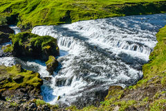 Countryside with trail near famous Skogafoss Waterfall, Iceland. On sunny summer day and blue sky Royalty Free Stock Photos