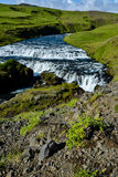Countryside with trail near famous Skogafoss Waterfall, Iceland. On sunny summer day and blue sky Royalty Free Stock Image
