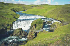 Countryside with trail near famous Skogafoss Waterfall, Iceland. On sunny summer day and blue sky, vintage and motion blur effect Royalty Free Stock Images
