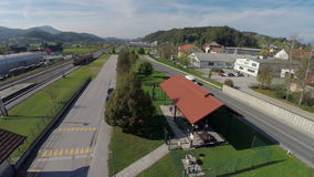 Countryside train station with vintage locomotive. RAW helicopter camera flaying above the train station on a countryside on a sunny day with steam locomotive in stock video footage