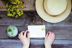 Countryside travel and vacation background. Female hands holding postcard surrounded with glass of lemonade, straw hat, wildflower Stock Photo