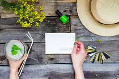 Countryside travel and vacation background. Female hands holding postcard surrounded with glass of lemonade, straw hat, wildflower Royalty Free Stock Photos