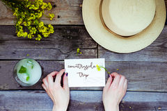 Countryside travel and vacation background. Female hands holding postcard surrounded with glass of lemonade, straw hat, wildflower Royalty Free Stock Photography