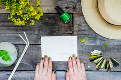 Countryside travel and vacation background. Female hands holding postcard surrounded with glass of lemonade, straw hat, wildflower Royalty Free Stock Images