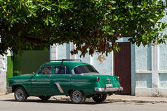 In the countryside under a tree parked green vintage car in Cuba Stock Images
