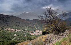 Mountain village on a cloudy day. Countryside. View of the valley, village and mountains in the distance on a cloudy evening Greece, island Crete Stock Image