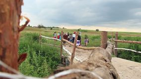 Countryside villagers walk bridge, field for ethnic festival old. Stock footage stock video