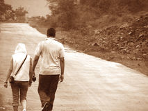 Countryside Walk. A young stylish couple, one tall the other short, walking on tar road at countryside Stock Images