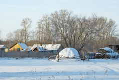 Countryside in winter. Rural scene with a haystack in the village Royalty Free Stock Image