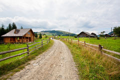 Countryside with wooden houses and sandy roads nearby mountain forests Stock Photos