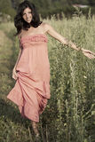 Countryside young woman walking in a grass field Royalty Free Stock Images