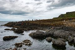 COUNTY ANTRIM, NORTHERN IRELAND - AUGUST 27, 2017: Group of tourists exploring the Giant`s Causeway. COUNTY ANTRIM, NORTHERN IRELAND - AUGUST 27, 2017: View of stock photo