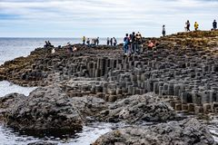 COUNTY ANTRIM, NORTHERN IRELAND - AUGUST 27, 2017: Group of tourists exploring the Giant`s Causeway. COUNTY ANTRIM, NORTHERN IRELAND - AUGUST 27, 2017: View of stock photos
