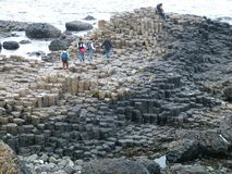 Tourists explore the unusual rock formations at Giant`s Causeway. royalty free stock images