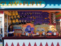 County fair game booth claw and flip it. Young woman standing at a county fair booth with purple monkeys and other toys and puppets Royalty Free Stock Images