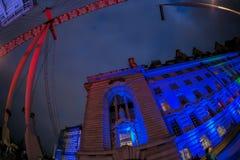 County Hall and part of London Eye illuminated in night. LONDON, ENGLAND - NOVEMBER 28, 2017: County Hall and London Eye illuminated in night at the boarding Stock Image