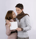 Couole holding blank sign and smiling. Young attractive couple smiling hugging and holding blank sign isolated on white gorgeous couple hugging and holding blank Royalty Free Stock Images