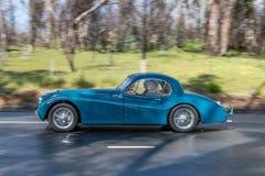Coupé 1953 de Jaguar XK 120 conduisant sur la route de campagne Photo libre de droits