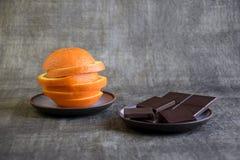 A coupé en tranches l'orange fraîche et le chocolat foncé image stock