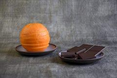 A coupé en tranches l'orange fraîche et le chocolat foncé image libre de droits