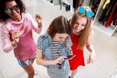 Coup courbe de jeunes amis féminins élégants portant les lunettes de soleil à la mode et les vêtements ayant l'amusement au centr Photo stock