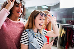 Coup courbe de jeunes amis féminins élégants portant les lunettes de soleil à la mode et les vêtements ayant l'amusement au centr Photos libres de droits