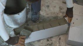 Coup courbe des mains de constructeur mettant le mortier des côtés de bloc avec la spatule banque de vidéos
