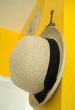 Coup de chapeau de paille sur le mur jaune Photographie stock