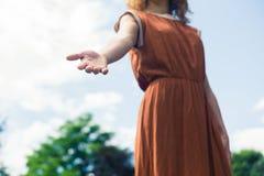 Coup de main de offre de jeune femme en nature Photo stock