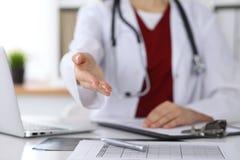 Coup de main de offre de docteur féminin de médecine en plan rapproché de bureau Médecin prêt à examiner et sauver le patient ami images libres de droits
