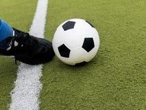 Coup-de-pied de footballeur la boule sur le gisement de stade de football Images stock