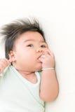 Coup de succion de bébé asiatique adorable sur le lit Images stock