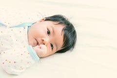 Coup de succion de bébé asiatique adorable sur le lit C'est réalisateur de croissance Images libres de droits