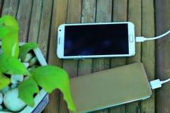 Coup fendu par écran de puissance de remplissage de téléphone Sur le fond en bambou Image stock