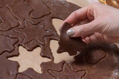 Coupant des biscuits de Noël, bonhommes en pain d'épice de cuisson, faisant le Christ images libres de droits