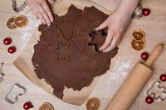 Coupant des biscuits de Noël, bonhommes en pain d'épice de cuisson, faisant le Christ photo libre de droits