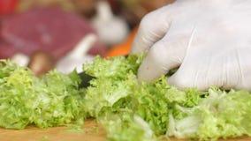 Coupant des verts, la laitue part avec un couteau, mains tournant dans les gants blancs Vue de côté Ingrédient pour l'hamburger U banque de vidéos