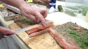 Coupant en tranches délicieuses des saumons banque de vidéos