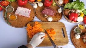 Coupant en tranches des carottes sur un conseil en bois sur un fond des légumes, la laitue part Vue de ci-avant banque de vidéos