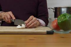 Coupant en tranches des champignons avec d'autres ingrédients autour Photos stock