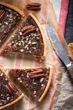 Coupant en tranches la tarte aux noix de pécan, sur la table en bois image libre de droits