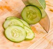 Coupant en tranches un certain concombre prêt à mettre dans une salade photo stock