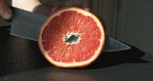 Coupant le fruit orange pour serrer le jus frais banque de vidéos