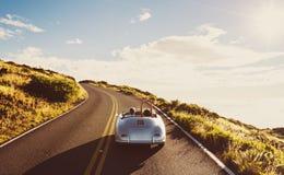 Coupe управляя на проселочной дороге в винтажном автомобиле спорт стоковое изображение