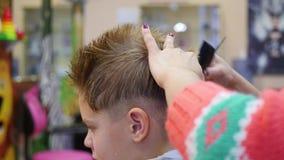 Coupe de cheveux d'un enfant avec des ciseaux dans le raseur-coiffeur banque de vidéos
