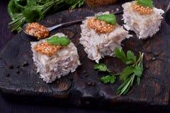 Coupe de gelée de poulet de Holodets en cubes complétés avec de la moutarde et le cilantro sur un conseil en bois foncé photo stock
