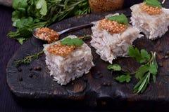 Coupe de gelée de poulet de Holodets en cubes complétés avec de la moutarde et le cilantro sur un conseil en bois foncé photos libres de droits