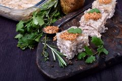 Coupe de gelée de poulet de Holodets en cubes complétés avec de la moutarde et le cilantro sur un conseil en bois foncé photographie stock