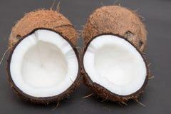 Coupe de noix de coco dans la moitié d'isolement sur le noir Photographie stock